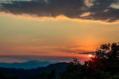 Sun, der hinter buntem Sommersonnenuntergang der Wolken sich versteckt lizenzfreie stockfotografie