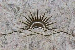 Sun, der hinter die Berge, geschnitzt in Steinoberfläche steigt Lizenzfreies Stockbild
