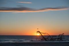 Sun, der hinter Jet Star Roller Coaster im Ozean steigt Lizenzfreie Stockfotografie
