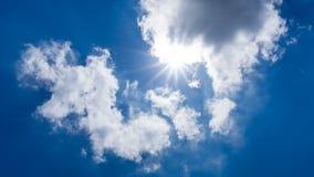 Sun, der hinter Wolke auf Hintergrund des blauen Himmels scheint Stockfotos