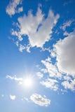 Sun, der im blauen Himmel mit flaumigen Wolken funkelt stockfoto