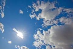 Sun, der von hinten eine Wolke in einem blauen Himmel scheint lizenzfreies stockfoto