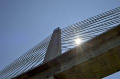 Sun derrière des câbles de flèche et de soutien de pont Photos libres de droits