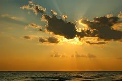 Sun derrière un nuage au-dessus de mer Photos stock