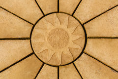 Sun design on golden coloured paving stone star pattern. Backgr. Ound or texture Royalty Free Stock Photography