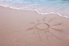 Sun dessiné dans le sable sur le bord de la mer Photo stock