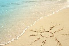 Sun dessiné dans le sable sur le bord de la mer Image libre de droits