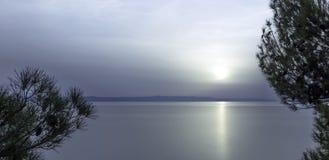Sun detrás de las nubes sobre el mar adriático en Makarska, Dalmacia, Croacia Foto de archivo
