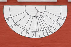 Sun-dial on wall. White sun-dial on red wall in Novodevichy Convent, Moscow, Russia stock photo