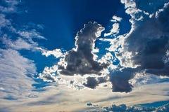 Sun dietro bianco blu delle nuvole Immagine Stock Libera da Diritti