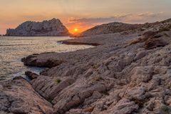 Sunset in Les Goudes, close to Marseille. Sun disappearing between two mountains in Les Goudes Stock Image