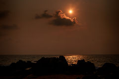 Sun disk near cloud over sea at sunrise dark rock on foreground Royalty Free Stock Photography