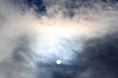 Sun disk at noon through the clouds. The sun disk at noon through the clouds royalty free stock photo