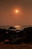 sun disk over sea at sunrise dark rocks on foreground stock photography
