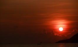 Sun disk among red sky fishing boats on horizon at sunrise Stock Image