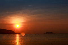Sun disk among red sky fishing boats on horizon at sunrise Royalty Free Stock Images