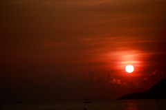 Sun disk among red sky fishing boats on horizon at sunrise Stock Photography