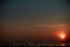 Sun disk among red sky fishing boats on horizon at sunrise Stock Images