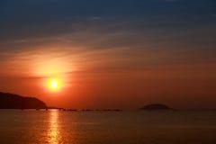 Sun disk among red sky fishing boats on horizon at sunrise Royalty Free Stock Image