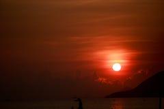 Sun disk among red sky fishing boats on horizon at sunrise Royalty Free Stock Photos