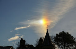 Sun dog and cirrus cloud above a church. Royalty Free Stock Photos
