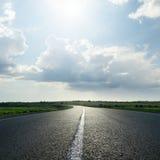 Sun in dramatic sky over asphalt road Royalty Free Stock Photos