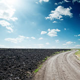 Sun in dramatic sky over road and black field Stock Photo