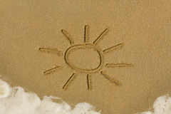 Sun drawing in the sand. Cartoon sun drawn in the sand on a beach Royalty Free Stock Image