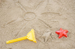 Sun drawn in sadn with beach toys next to it. Sun drawn in sand with beach toys next to it. Concept of fun summer holidays Royalty Free Stock Image