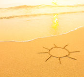 Sun drawn in the sand of a beach, soft surf wave. Travel. Royalty Free Stock Photos