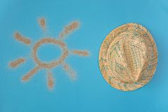 Sun drawn by the sand on blue background. Hat isolated on blue background. Top view stock photography
