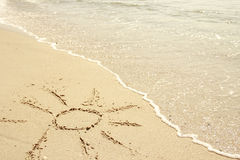 Sun drawn in the sand on the seashore Stock Photos