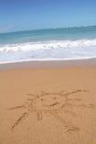Sun drawn on the sandy beach Stock Photos