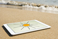 Sun drawn in a tablet in the sand of a beach Stock Photos