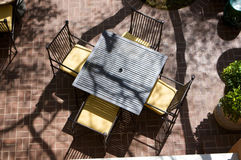 Sun drenched table for four at an outdoor cafe fro Stock Images