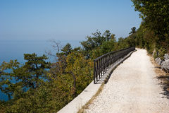 Sun-drenched trail facing the blue sea. An elevated sun-drenched trail facing the blue sea. Taken on the via Napoleonica in Trieste, Italy Royalty Free Stock Image