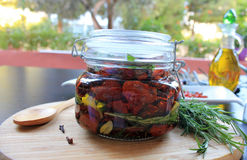 Sun-dried cherry tomatoes with spices in olive oil in a glass jar Stock Image