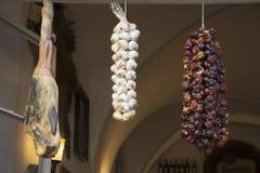 Sun-dried leg pork and garlic and seasoning hanging at window Royalty Free Stock Photo