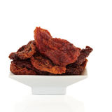 Sun Dried Tomatoes. In a white porcelain dish isolated over white background Royalty Free Stock Images