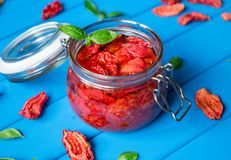 Sun dried tomatoes with basil in a glass jar on a blue wooden table. Vegetarian concept Royalty Free Stock Photography