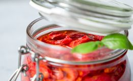 Sun dried tomatoes with basil in a glass jar on a concrete table. Vegetarian concept Royalty Free Stock Images