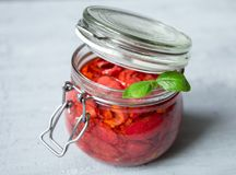 Sun dried tomatoes with basil in a glass jar on a concrete table. Vegetarian concept Royalty Free Stock Photography