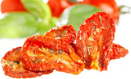 Sun-dried tomatoes with basil leaves. And tomato on background, over  white Royalty Free Stock Image