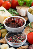 Sun-dried tomatoes in a bowl and various appetizers, vertical stock photos