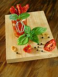 Sun-dried tomatoes with garlic, basil and spices. On a wooden board Royalty Free Stock Photo