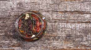 Sun dried tomatoes with herbs and olive oil in jar Stock Photo