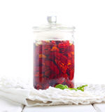 Sun dried tomatoes with herbs, seasonings in olive oil in a jar. Over white Stock Photography