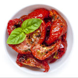 Sun Dried Tomatoes Isolated. Sun dried tomatoes garnished with basil, in small bowl, isolated on white Royalty Free Stock Photo