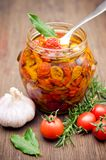 Sun dried tomatoes in olive oil. On wooden surface Royalty Free Stock Image