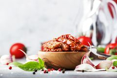 Sun dried tomatoes in olive oil with green basil and spices in wooden bowl on gray kitchen table, place for text stock images